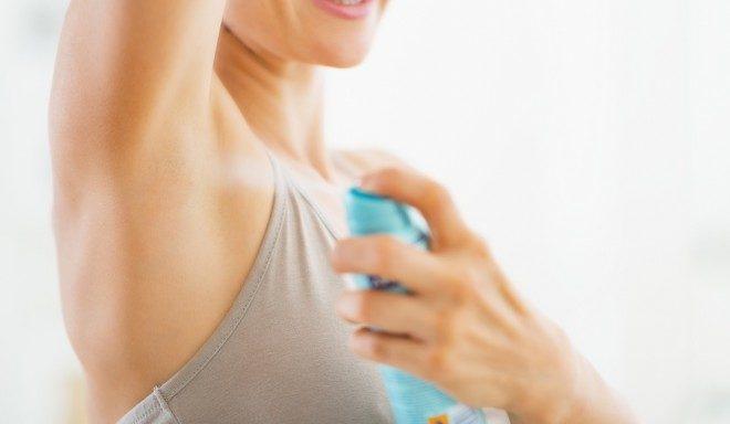 Une femme mettant du déodorant