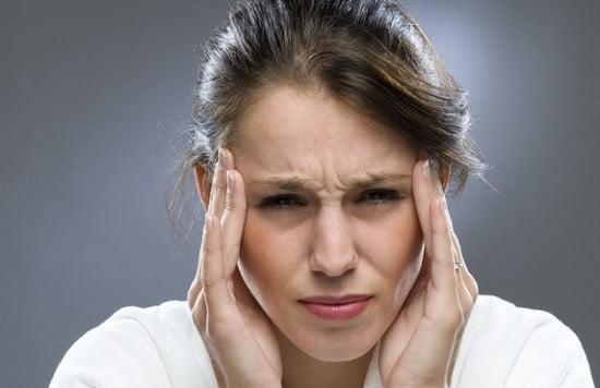 Une femme prise de mal de tête.