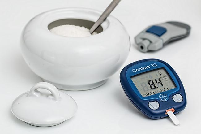 Un pot de sucre et un lecteur de glycémie.