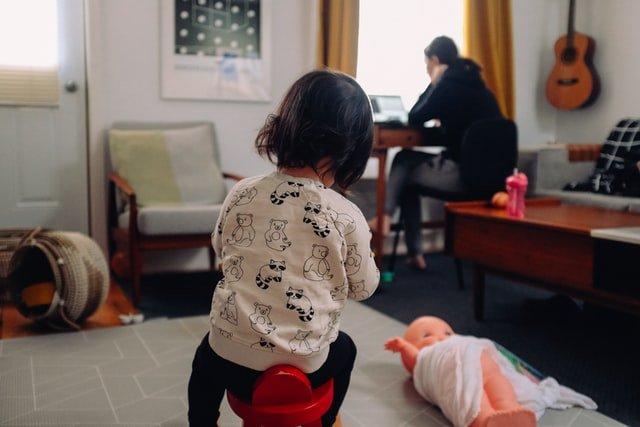 Une fille assise sur un jouet.